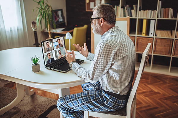 Man in video conference wearing dress shirt and pajama bottoms